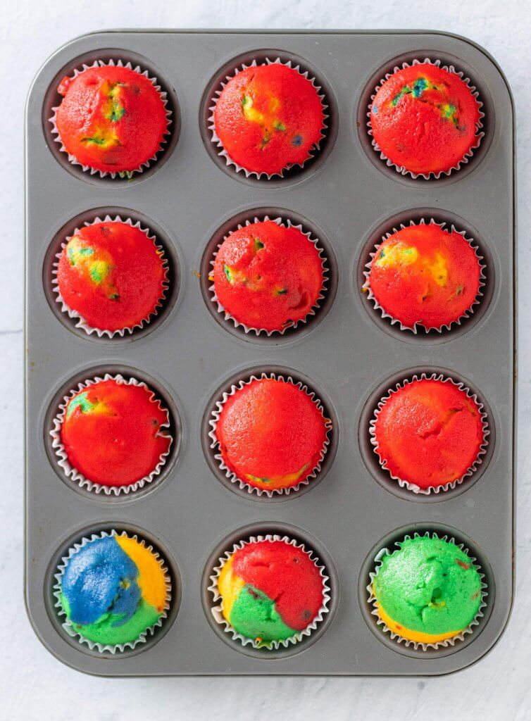 baked multicolored rainbow cupcakes sitting inside of a muffin tin