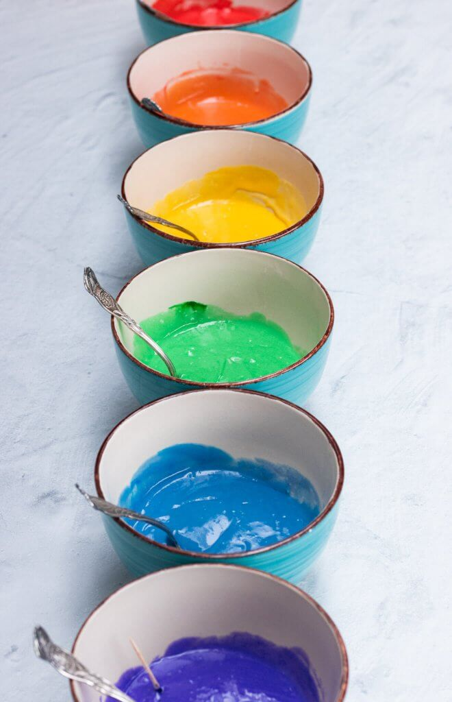 Bowls of rainbow dyed cake batter to make rainbow cupcakes